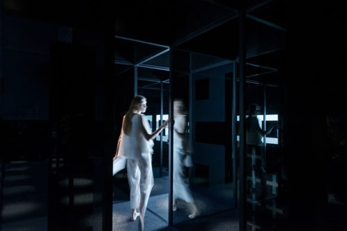 A woman stands inside the glass MAZE at Shanghai Museum of Glass Park, designed by COORDINATION ASIA